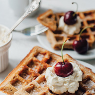 Waffles with whipped cream and cherry