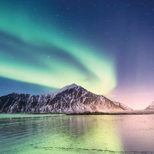 Northern light above mountains and sea shore